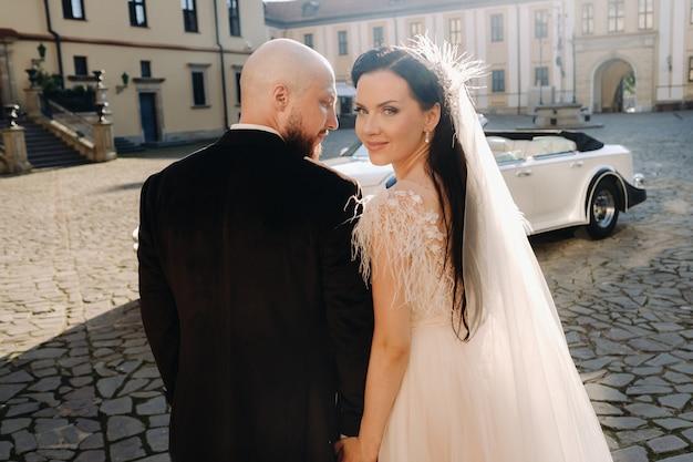 レトロな車の近くの城の中庭でエレガントな結婚式のカップル