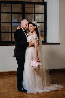 ニャスヴィシュの街の古い城の内部にあるエレガントな結婚式のカップル。