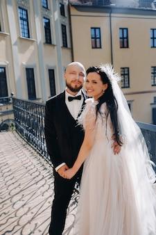 ニャスヴィシュの街の古い城のバルコニーでエレガントな結婚式のカップル
