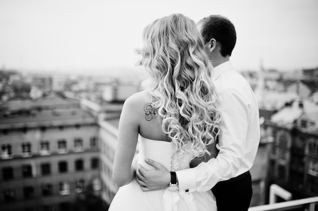 Elegant wedding couple on the roof with high-tech architecture line
