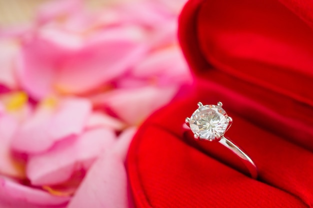 Elegant wedding diamond ring in red heart jewelry box on beautiful pink rose petal