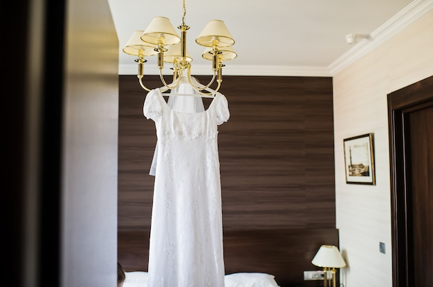 Elegant wedding dress hanging on the chandelier in the interior of the hotel
