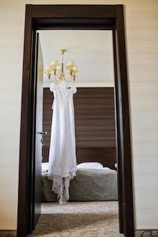 Элегантное свадебное платье висит на люстре в интерьере отеля