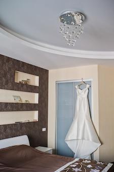 Элегантное свадебное платье висит на шкафу