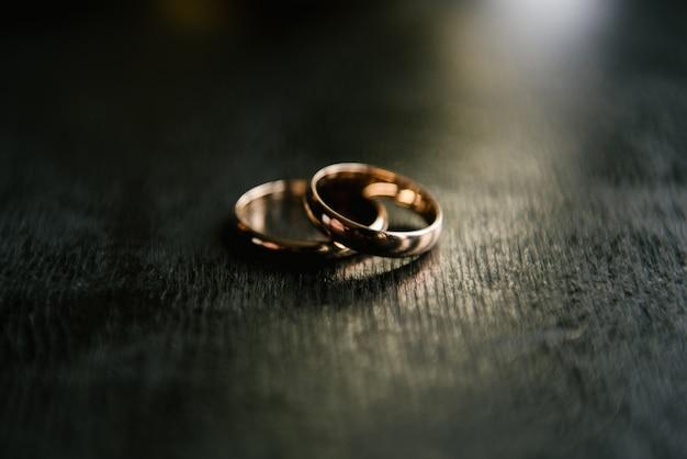 Элегантные обручальные кольца для жениха и невесты на черном фоне с бликами, макро, выборочный фокус