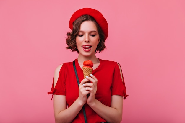 디저트를 즐기는 우아한 단정 한 여자. 아이스크림을 먹는 곱슬 프랑스 소녀.