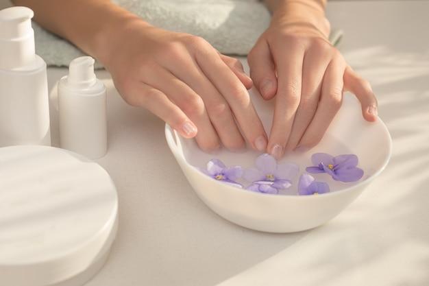 긴 손가락으로 우아하고 단정 한 여성 손. 손, 손톱, 매니큐어에 대한 피부 관리 절차. 스파 뷰티 살롱의 개념입니다. mocap, 플라스틱 용기. 그림자의 아름다운 플레이, 테이블에 빛.