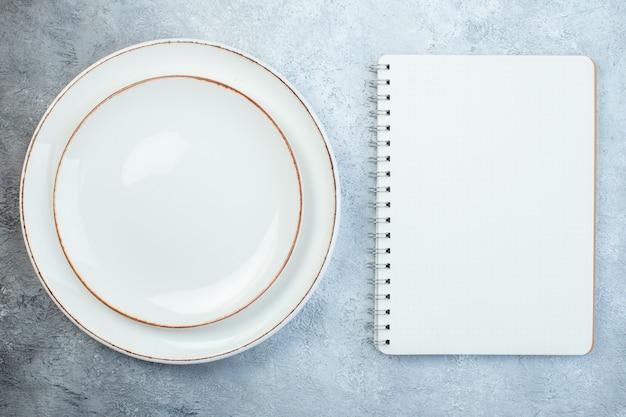 Eleganti piatti bianchi e taccuino su superficie grigia con superficie invecchiata con spazio libero