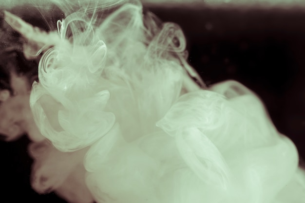 Elegant white smoke on black screen