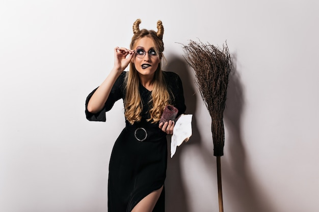 Elegant wizard in glasses funny posing on white wall. fair-haired witch standing near broom.