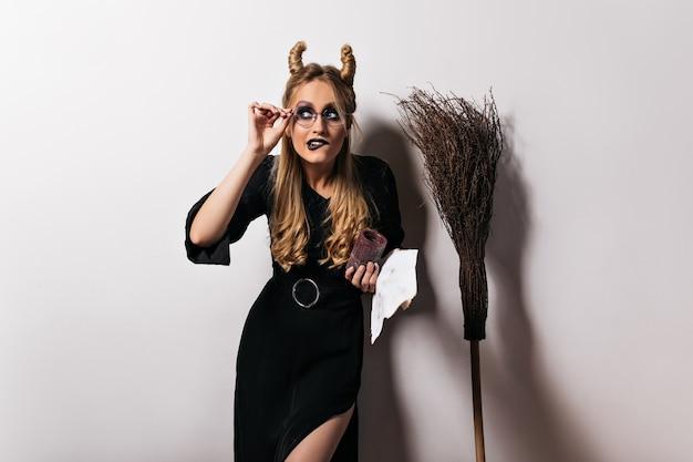흰 벽에 재미있는 포즈 안경에 우아한 마법사. 빗자루 근처에 서있는 국방과 마녀.