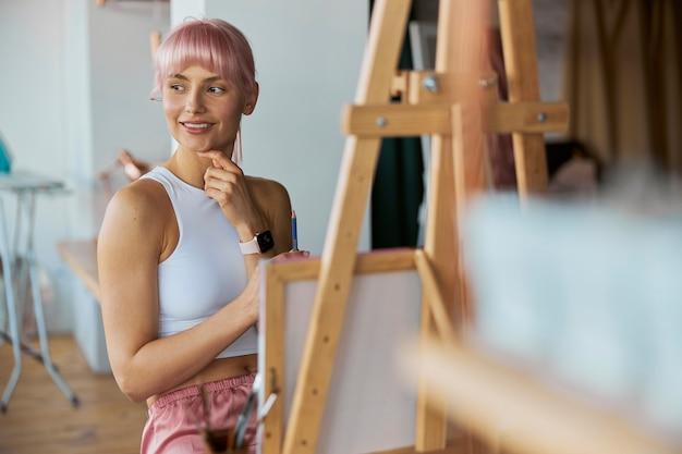 우아한 여성 예술가는 집에서 빈 흰색 캔버스가 있는 이젤 옆에 앉는다