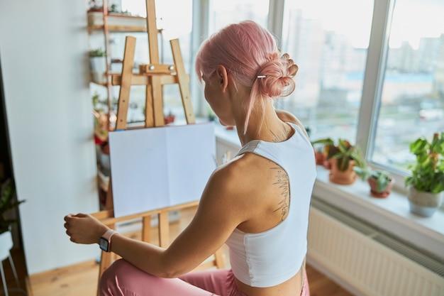 エレガントな女性アーティストは、自宅で空白の白い帆布とイーゼルのそばに座っています