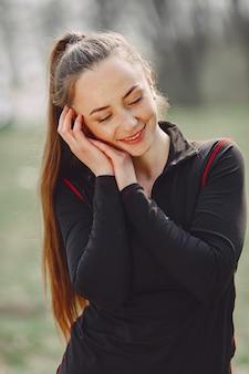 Donna elegante in vestiti neri in un parco di primavera