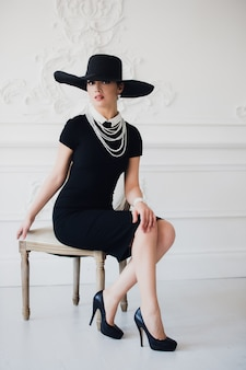 Elegant woman in black dress with a hat sitting on a chair