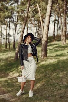 Donna elegante in un cappello nero in una foresta di primavera