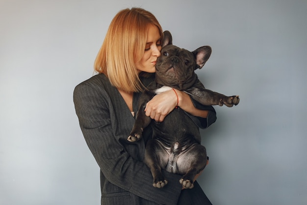 Elegant woman in a black suit with black bulldog