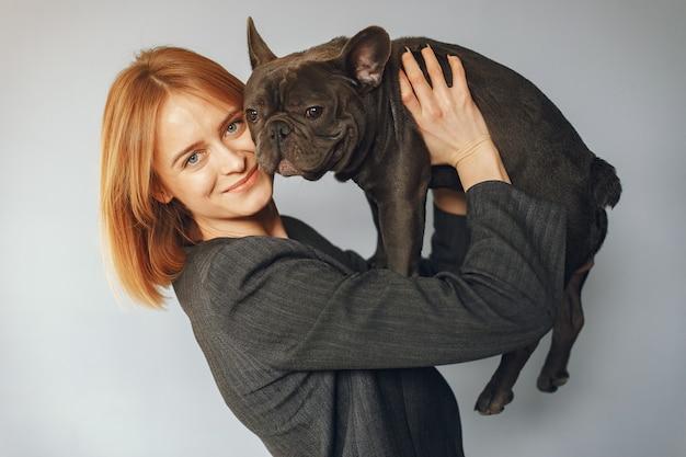 Donna elegante in un abito nero con bulldog nero