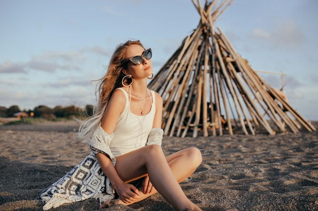 Elegant woman in black sunglasses sitting on the beach and looking at sky.