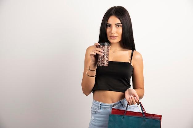 Donna elegante nella parte superiore nera che tiene i sacchetti e il caffè. foto di alta qualità