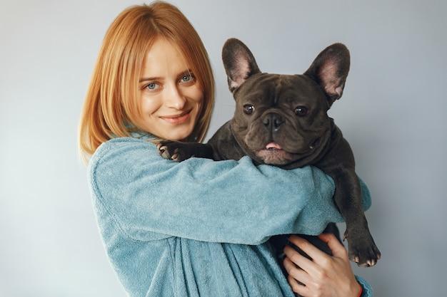 Elegant woman in a blue bathrobe with black bulldog