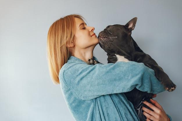 Donna elegante in un accappatoio blu con bulldog nero