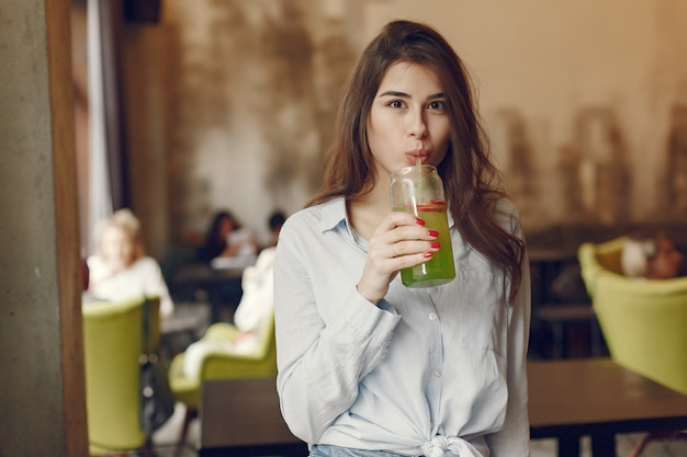 Elegant woman in a blue blouse spending time in a cafe