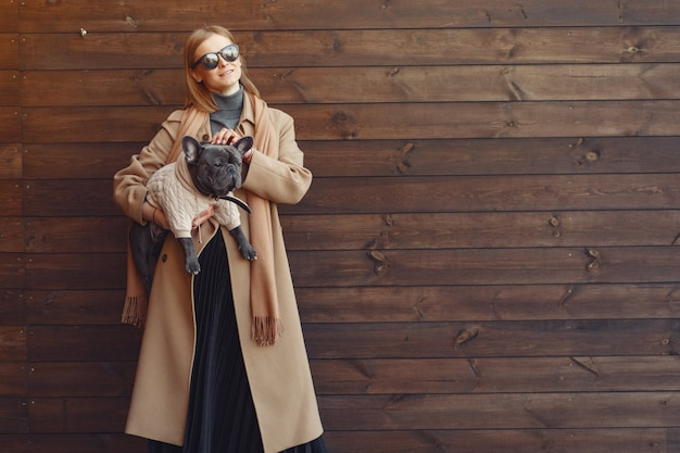 Elegant woman in a brown coat with black bulldog