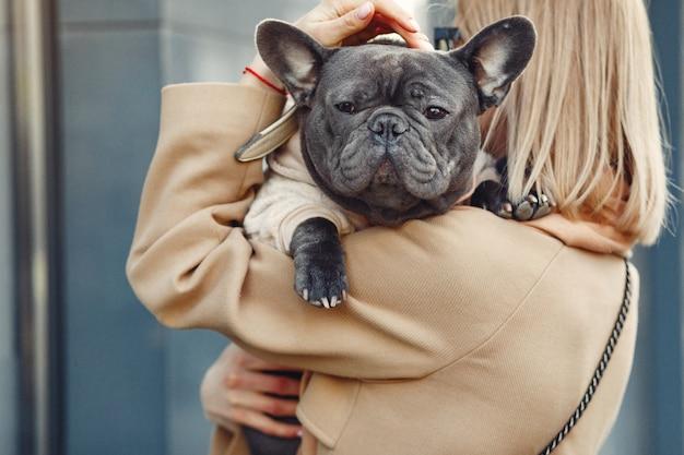Elegant woman in a brown coat with black bulldog