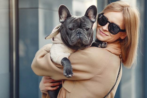 Donna elegante in un cappotto marrone con bulldog nero