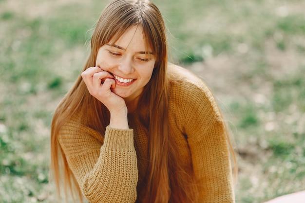 Donna elegante in un maglione marrone in un parco di primavera
