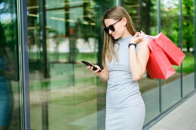 エレガントな女性の買い物袋を運ぶ