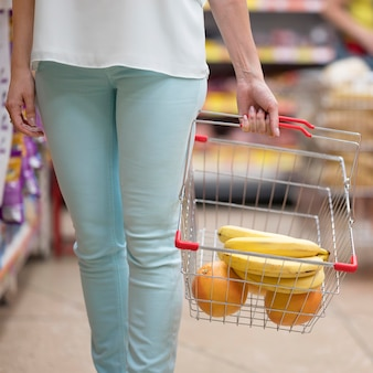 Elegant woman carrying shopping cart with fruits