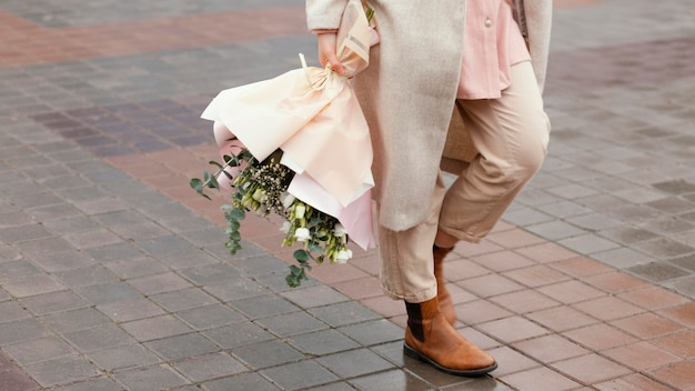 Elegant woman in the city holding bouquet of flowers