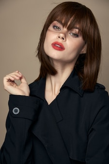 スタジオクローズアップを楽しんでいるベルトエレガントなスタイルのエレガントな女性のコート