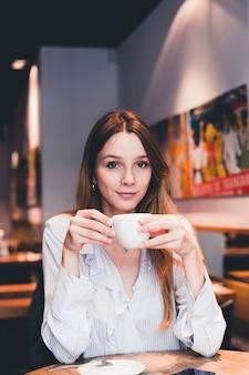 Elegant woman drinking in cafe
