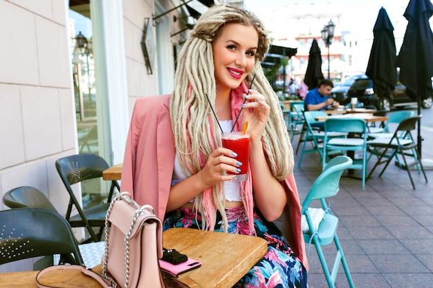 Элегантная женщина, наслаждаясь ягодным лимонадом на террасе кафе