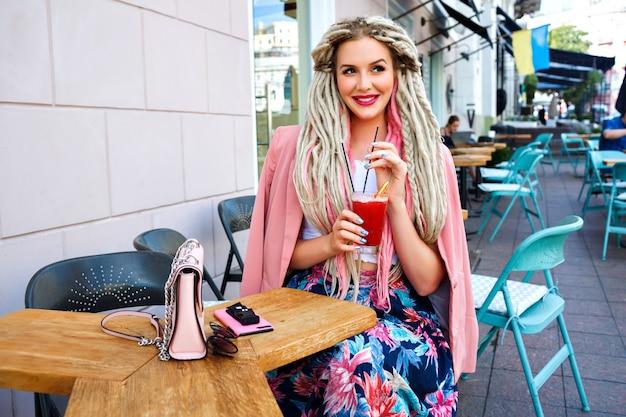 Elegant woman enjoying her berry tasty lemonade on cafe terrace