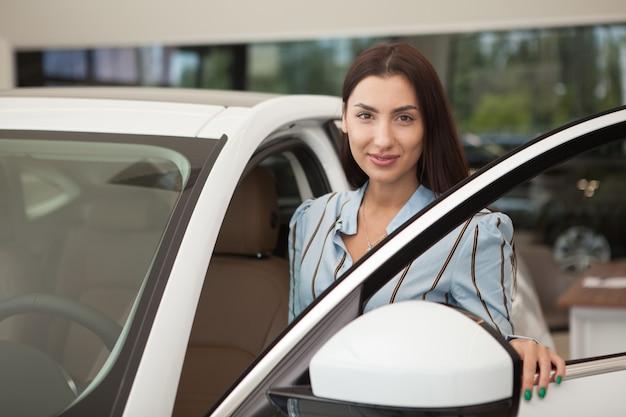 優雅な女性がdelershipで新しい自動車に乗り込む