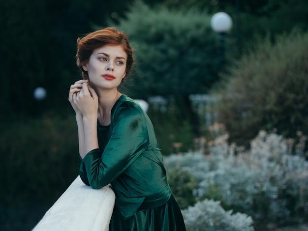 エレガントな女性の緑のドレス建築緑の葉は高級モデルを歩きます。