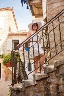 Elegant woman in hat posing on beautiful stairs at narrow street