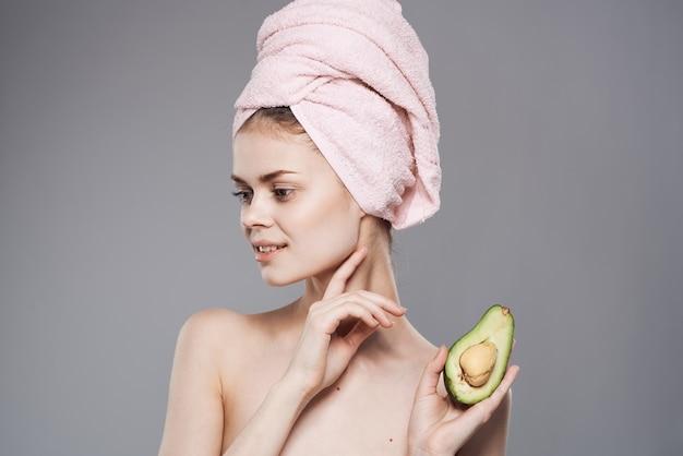 그녀의 손에 그녀의 머리에 분홍색 수건을 들고 우아한 여자 이국적인 과일 깨끗한 피부 화장품