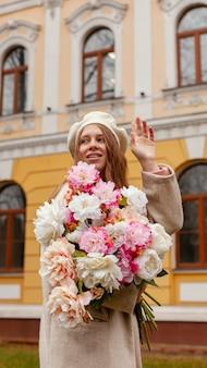 Donna elegante che tiene il mazzo di fiori all'aperto in primavera