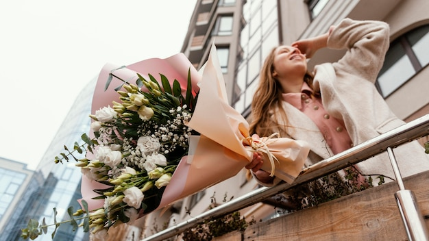 Elegant woman holding bouquet of flowers outdoors