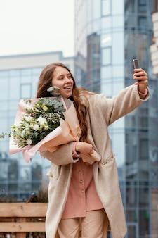 Donna elegante che tiene il mazzo di fiori all'esterno e prendendo selfie con lo smartphone