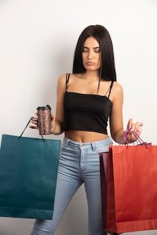 Donna elegante che tiene caffè e borse della spesa. foto di alta qualità