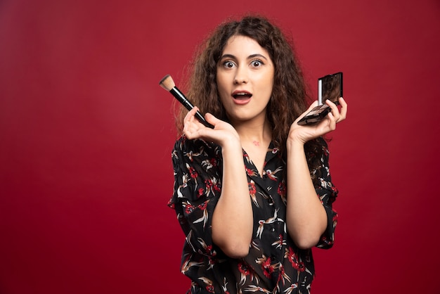 Elegant woman holding makeup brush and bronzer.