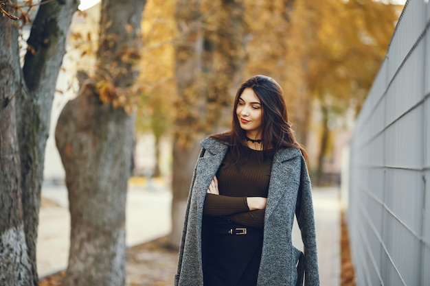 秋の街の優雅な女性