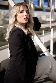 街を眺める屋上バーテラスで黒いジャケットを着たエレガントな女性。