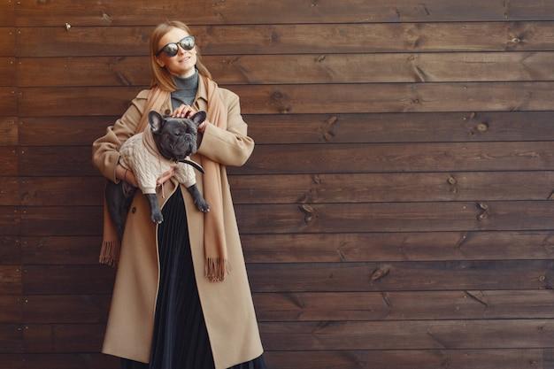 Элегантная женщина в коричневом пальто с черным бульдогом